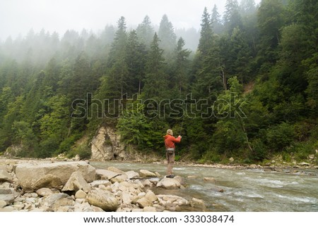 Fishing in the beautiful mountain river. Trout fishing in the mountains. Exciting fishing and beautiful scenery. Photos for natural and fishing magazines, posters and websites.  - stock photo