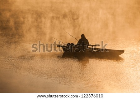 Fishing in the morning mist - stock photo