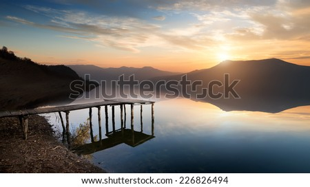 Fishing jetty on mountain river at sunset - stock photo