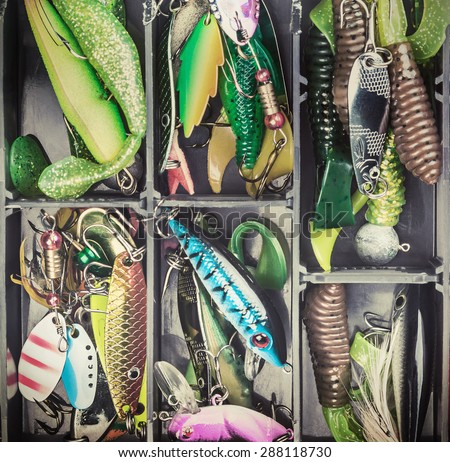 fishing lures and accessories in the box background. Toned image
