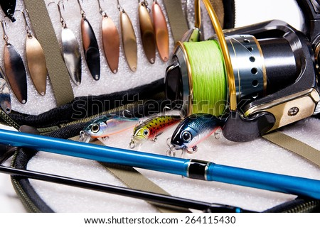 Fishing metal and plastic baits with bag for baits on white background. Different kinds of the fishing baits. - stock photo