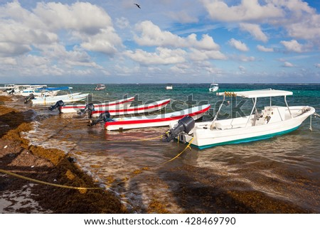 Fishing motor boats moored to dirty tropical beach