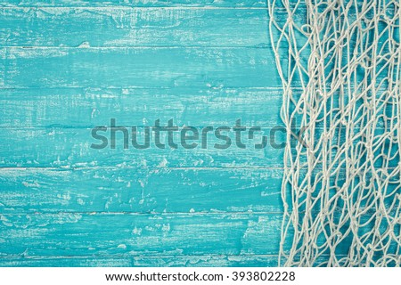 Fishing net from right side of old turquoise painted board background with copy space - stock photo