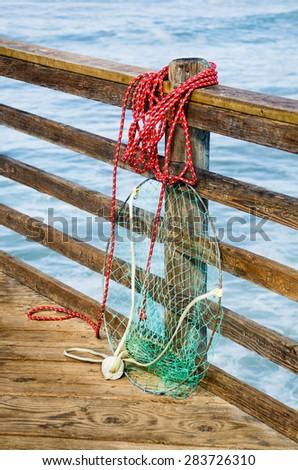 Fishing net on an ocean pier, sea water on background - stock photo