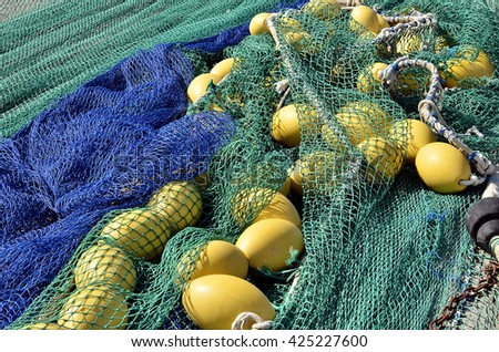 Fishing nets and yellow floats in spanish port - stock photo