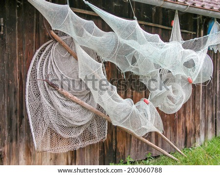 Fishing Nets hang on the side of a hut for drying. - stock photo
