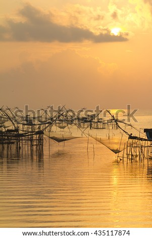 Fishing nets in the lake in Southern part of Thailand in golden warm morning light - stock photo