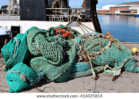 Fishing nets lying on a dock in a harbor next to a fishing trawler. - stock photo