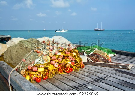 Fishing nets on a dock in Aruba with ocean, sky and clouds in the background - stock photo