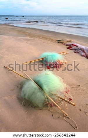 Fishing nets on the sandy beach after fishing day. - stock photo
