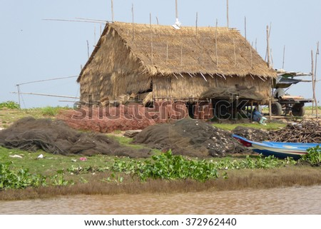 Fishing nets outside traditional house on stilts, Kompong Kleang floating fishing village,  Cambodia - stock photo