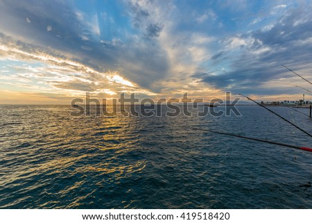 Fishing off of a pier in the ocean at sunset. - stock photo