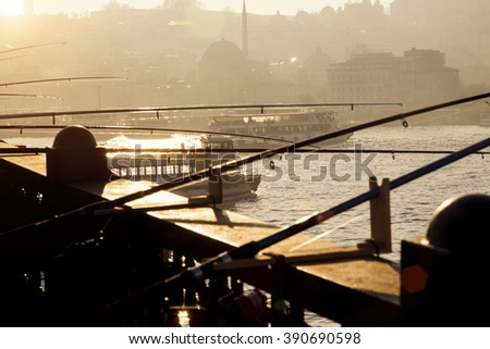 Fishing on Galata Bridge in Istanbul; Turkey. New Mosque (Yeni Cami) in the background while sun is setting.