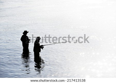 Fishing on the lake, two fishermen in the water  - stock photo