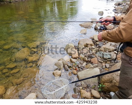 Fishing on the mountain river. Fisherman on the shore. Summer Activities. Fishing
