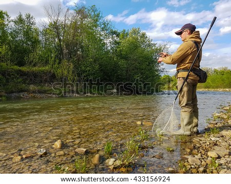 Fishing on the mountain river. Trout fishing. Fisherman fishing in the mountains - stock photo