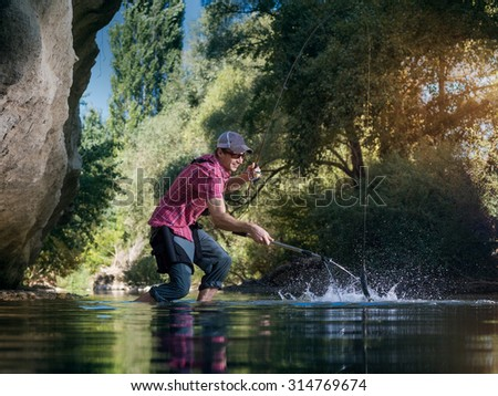 Fishing on the river. Fisherman catches a fish in forest. Man pulls a fish net. - stock photo