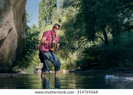 Fishing on the river. Professional sports fisherman  catches a fish.