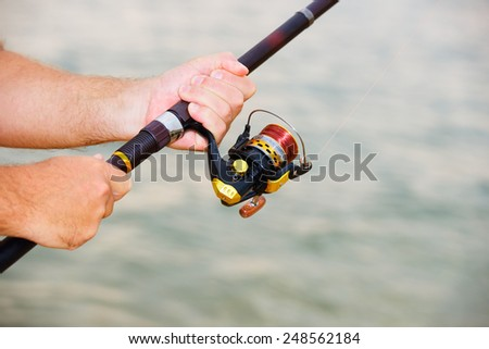 Fishing on the sea: rod in fisherman hands