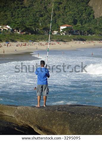 Fishing on top of the rock at the beach, in Niteroi, Rio de Janeiro, Brazil - stock photo
