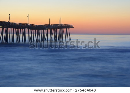 Fishing Pier and Smooth Ocean at Sunrise - stock photo