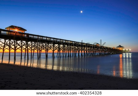 Fishing pier at Folly Beach near Charleston, South Carolina at sunrise with a small moon overhead.