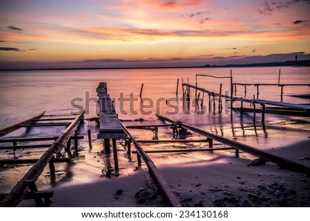 Fishing pier in sea at sunset - stock photo