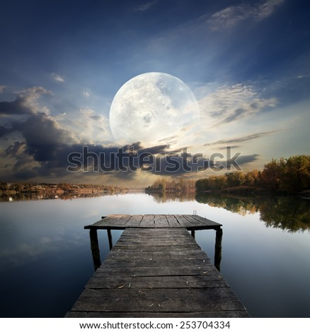 Fishing pier on a river under fool moon. Elements of this image furnished by NASA - stock photo