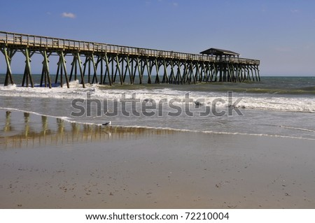 Fishing Pier stretches out into the ocean - stock photo