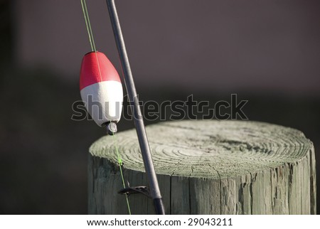 Fishing Pole with bobber leaning against a post with copy space - stock photo