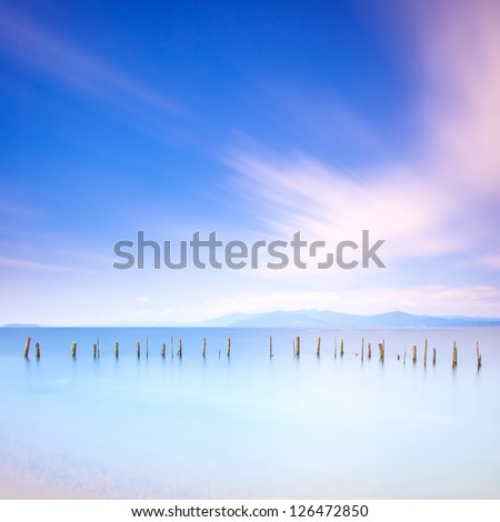 Fishing poles and soft water on a quiet sea landscape. Long exposure photography - stock photo