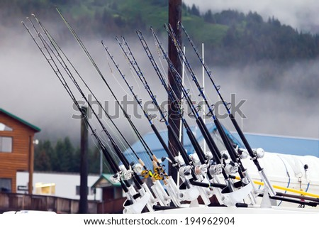 Fishing poles lined up in a row background - stock photo