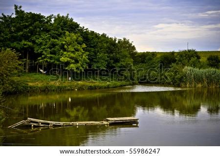 fishing pond with beautiful nature around it - stock photo