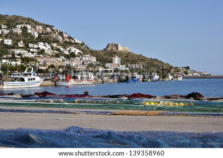 Fishing port and town of Roses, or Rosas, with fishing nets and the Castell de la Trinitat in the background. Roses is a commune on the Costa Brava at northeastern Catalonia in Spain. - stock photo