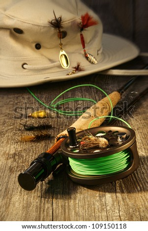 Fishing reel and hat on bench - stock photo