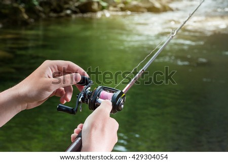 Fishing reel multiplier with a fishing rod in the hands of the fisherman. Trout fishing in the river. Close up.