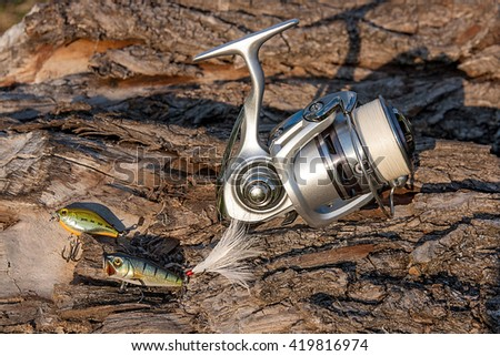 Fishing reel on the natural background. Assorted of various kind of fishing plastic baits. Spinning on the old tree with brown bark. - stock photo