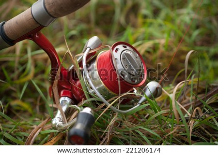 Fishing reel with setup for predator fish casting (angling) like pike, perch, zander etc. Location: river coast, on the ground - stock photo