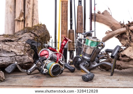 fishing reels and fishing rods with wooden board and snag - stock photo