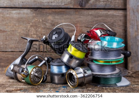 fishing reels and spoole with line on background of wooden timbers - stock photo