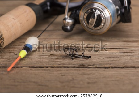 Fishing rod and reel along with fishing hooks - stock photo