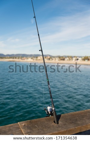 Fishing rod and reel on a wooden bar on a ocean - stock photo