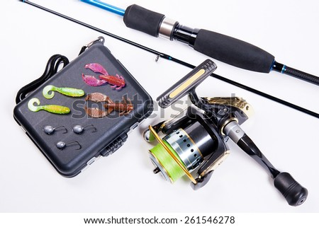 Fishing rod and reel with box for baits on white. Fishing silicone lures. - stock photo