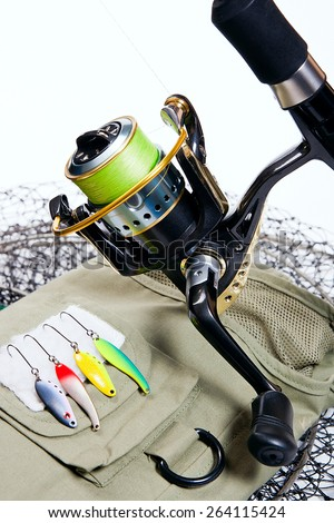 Fishing rod and reel with metal baits on white background. Different kinds of the metal baits. - stock photo
