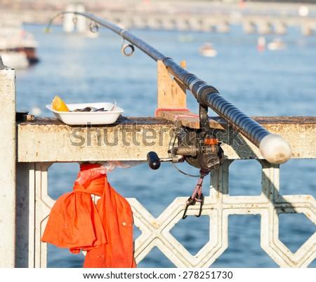 Fishing rod, attached to the railing of the Galata Bridge, Istanbul, Turkey - stock photo