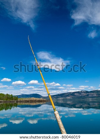 Fishing rod bends under weight of fish that just took lure in Lake Laberge, Yukon Territory, Canada
