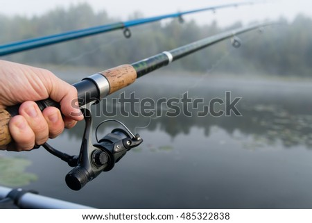 fishing rod in hand man close-up, shallow dof