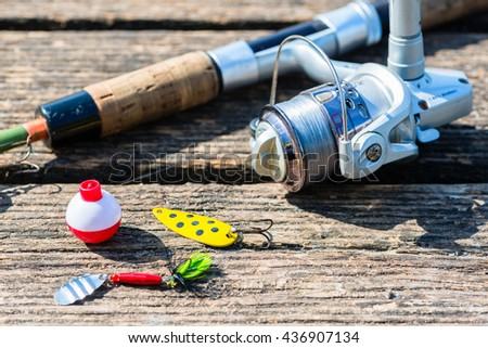 fishing rod, lure, and hook on jetty, preparations for sport angling - stock photo