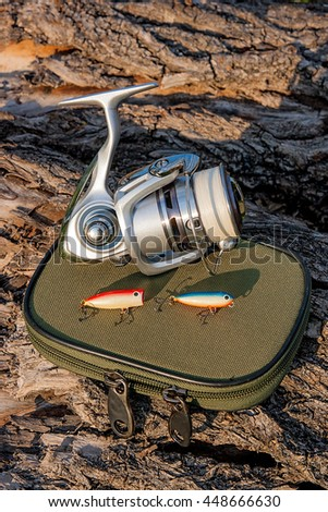 Fishing rod with fishing reel on the natural background. Assorted of various kind of fishing baits. Objects on the green box for fishing bait on the old tree with brown bark. - stock photo