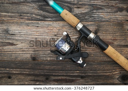 Fishing rod with reel, isolated on wooden background